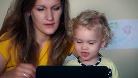 Mutter mit dem Kleinkindkind, das Zeit zusammen mit Tablet-Computer genießt stock footage