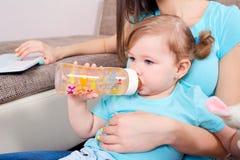 Mutter mit dem Laptop und Kind, die Babyflasche halten stockfoto