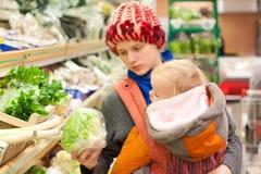 Mutter mit dem Mädcheneinkaufen im Supermarkt Stockbilder