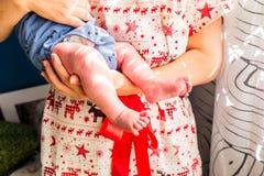 Mutter mit dem roten Kleid, das ihren Sohn hält Stockfotos