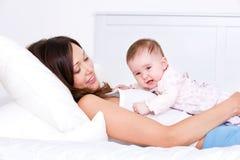Mutter mit dem Schätzchen, das auf dem Bett liegt Stockbilder