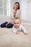 Mutter mit dem Schätzchen, das erlernt zu kriechen Stockbild