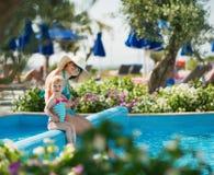 Mutter mit dem Schätzchen, das im Pool der geöffneten Luft sitzt stockbilder