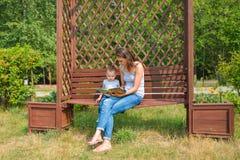 Mutter mit dem Sohn, der auf einer Bank im Park- und Lesebuch sitzt Lizenzfreie Stockfotos