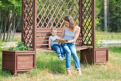 Mutter mit dem Sohn, der auf einer Bank im Park- und Lesebuch sitzt Lizenzfreie Stockbilder