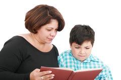 Mutter mit dem Sohn, der das Buch liest Stockfotos