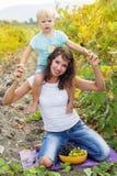 Mutter mit dem Sohn, der Spaß im Traubenweinberg hat Lizenzfreies Stockfoto