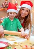 Mutter mit dem Sohn, der Weihnachtsplätzchen tut Stockfotos