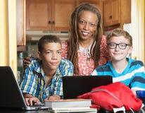 Mutter mit dem Sohn und Freund, die Hausarbeit tun Lizenzfreie Stockfotografie