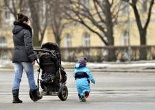 Mutter mit dem Spaziergänger, der nahe kleinem Sohn geht Lizenzfreie Stockbilder
