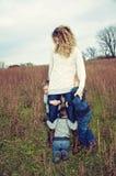Mutter mit den Kindern, die an ihr hängen Lizenzfreies Stockbild