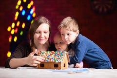 Mutter mit den Kindern, die Lebkuchenhaus bilden Stockbild