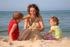 Mutter mit den Kindern, die mit Sand spielen Lizenzfreie Stockfotografie