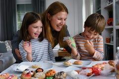 Mutter mit den Kindern, die Plätzchen für Halloween verzieren stockfotos