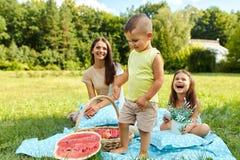 Mutter mit den Kindern, die Spaß im Park haben Glückliche Familie draußen lizenzfreie stockfotos