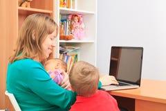Mutter mit den Kindern, die zu Hause an Laptop arbeiten Lizenzfreies Stockbild