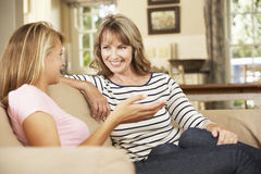 Mutter mit der jugendlichen Tochter, die auf Sofa At Home Chatting sitzt stockfotos