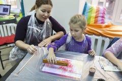 Mutter mit der jungen Tochter, die lernt, ebru Zeichnung in der Werkstatt zu machen Lizenzfreie Stockfotos