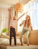 Mutter mit der Kindertochter, die den Spaß zu Hause springt auf Bett, glückliche Elternschaft hat stockfotografie