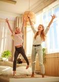 Mutter mit der Kindertochter, die den Spa? zu Hause springt auf Bett, gl?ckliche Elternschaft hat stockbilder