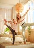 Mutter mit der Kindertochter, die den Spa? zu Hause springt auf Bett, gl?ckliche Elternschaft hat lizenzfreies stockfoto