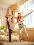 Mutter mit der Kindertochter, die den Spa? zu Hause springt auf Bett, gl?ckliche Elternschaft hat lizenzfreie stockfotos