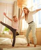Mutter mit der Kindertochter, die den Spa? zu Hause springt auf Bett, gl?ckliche Elternschaft hat lizenzfreie stockbilder