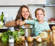 Mutter mit der kleinen Tochter, die zu Hause kocht Lizenzfreies Stockbild