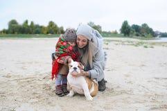 Mutter mit der kleinen Tochter und dem Welpen einer Bulldogge im Herbst draußen Stockbild