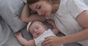 Mutter mit der netten Babytochter, die auf Bett schläft stock footage