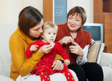 Mutter mit der reifen Großmutter, die für krankes Baby sich interessiert Stockbild