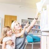 Mutter mit der Tochter, die Buch in der Bibliothek wählt stockbild