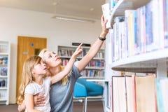 Mutter mit der Tochter, die Buch in der Bibliothek wählt stockfotografie