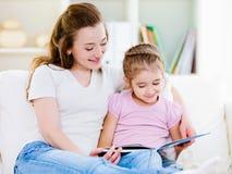 Mutter mit der Tochter, die das Buch liest Lizenzfreies Stockfoto