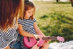 Mutter mit der Tochter, die in einem Sommerpark spielt stockfoto