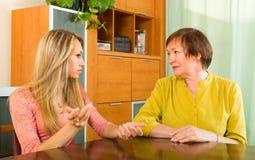 Mutter mit der Tochter, die ernsthaft spricht Stockbilder