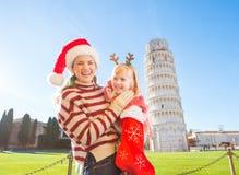 Mutter mit der Tochter, die Geschenk von der Weihnachtssocke, Pisa auszieht Lizenzfreies Stockfoto