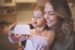 Mutter mit der Tochter, die lustiges Gesicht macht Stockfotografie