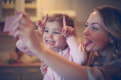 Mutter mit der Tochter, die lustiges Gesicht macht Lizenzfreie Stockfotografie