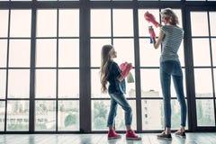 Mutter mit der Tochter, die Reinigung tut stockfotos