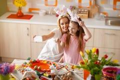 Mutter mit der Tochter, die selfie für Ostern macht Stockbilder