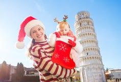 Mutter mit der Tochter, die in Weihnachtssocke nach Geschenk, Pisa sucht Stockbilder