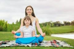 Mutter mit der Tochter, die Yogaübung tut Stockfotos