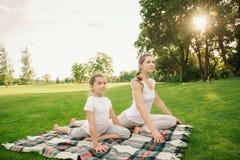 Mutter mit der Tochter, die Yogaübung tut Lizenzfreies Stockbild