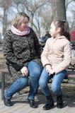 Mutter mit der Tochter sitzen auf einem Shop im Park Stockfotos