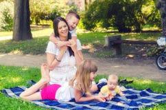 Mutter mit drei Kindern, die im Sommerpark spielen Lizenzfreies Stockbild