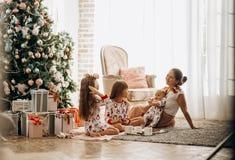 Mutter mit einem Baby auf ihren Händen sitzt O der Teppich mit ihren zwei Töchtern, die in den Pyjamas Plätzchen mit Kakao ess lizenzfreie stockfotos