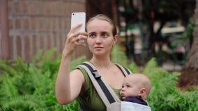 Mutter mit einem Baby in einem Riemen, der einen Smartphone in ihren Händen hält und über Videoverbindung mit Freunden in Verbind stock video