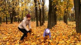 Mutter mit einem Kind, das mit Blättern spielt stock video footage