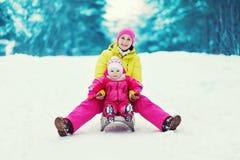 Mutter mit einem Kind, das Spaß im Winter rodelt und hat Stockbilder
